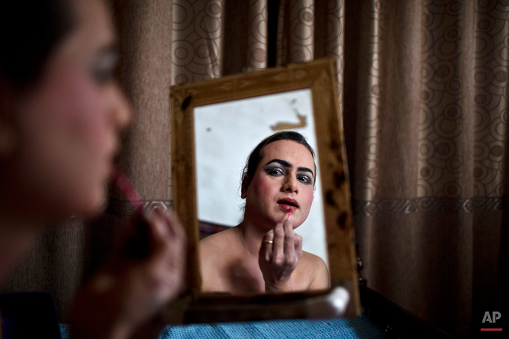 In this Saturday, Jan. 10, 2015 photo, Pakistani Waseem Akram, 27, applies makeup on his face as he prepares himself for a party at a friend's place in Rawalpindi, Pakistan. By day, Akram sells mobile phone accessories from an alleyway shop in an old neighborhood of this Pakistani city. But by night, he stands before a mirror, shaving away his beard and picking through mascara and rouge to become Rani, a female wedding party dancer. ìLife is so hard, one job is not enough to help me and my family,î Akram says. (AP Photo/Muhammed Muheisen)