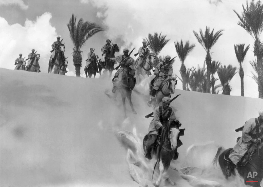 A patrol of Spahis, famous French Colonial cavalrymen, gallop their mounts down the side of a dune in the Egyptian desert, Jan. 3, 1941. These troops are reported to be among the French forces which remained allies to Great Britain after the armistice between France and the Axis powers. (AP Photo)
