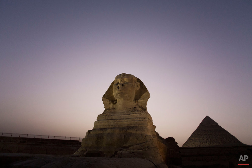 Journalists visit the Sphinx, with the body of a lion and a human head, on a media tour following the completion of restoration work in preparation for the reopening of the courtyard around its base, in front of the Khafra pyramid, Giza, near Cairo, Egypt, Sunday, Nov. 9, 2014. (AP Photo/Hiro Komae)
