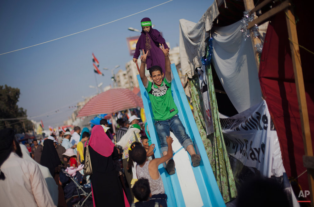 Egyptian children play on a slide set up next to a tent outside Rabaah al-Adawiya mosque, where supporter of Egypt's ousted President Mohammed Morsi have installed a camp and held daily rallies at Nasr City, in Cairo, Egypt, Saturday, Aug. 10, 2013. Morsi supporters demanded his reinstatement, restoration of the suspended constitution drafted under Morsi and the return of the disbanded Islamist-dominated legislative council. The interim government rejected those demands, moving forward with a fast-track plan calling for revising the constitution and holding presidential and parliamentary elections early next year. (AP Photo/Khalil Hamra)