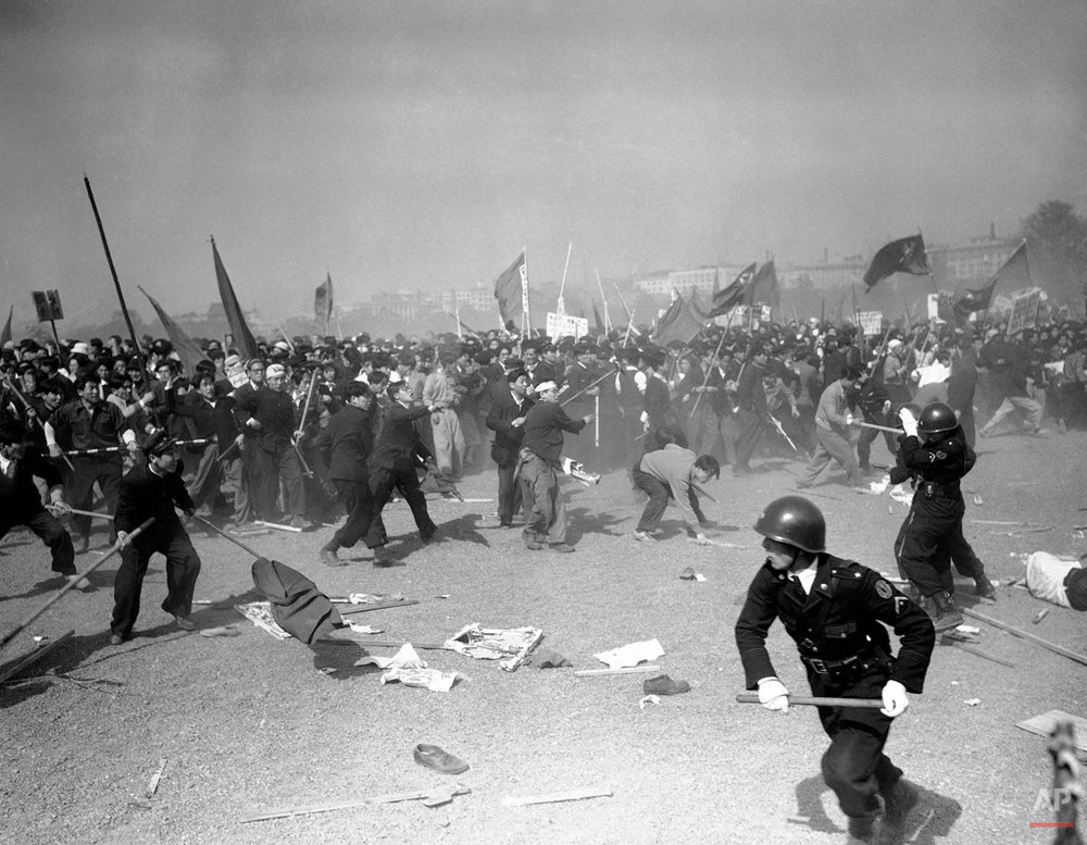 Demonstrators stone Japanese policemen at the height of the pro-Red May Day riots in downtown Tokyo on May 1, 1952. Casualties were numerous on both sides as police used tear gas, guns and clubs to beat back the waves of rioters. (AP Photo/Max Desfor)