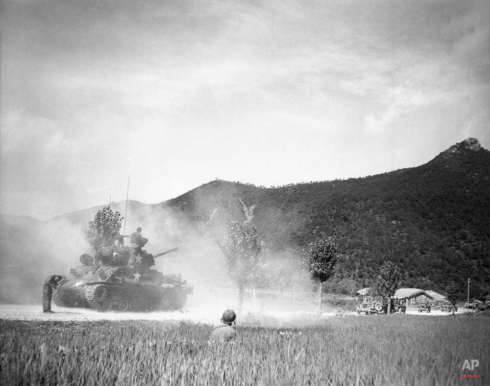 An American medium tank blasts at enemy positions in South Korean hills, August 12, 1950 as a soldier, crouched in weeds in right foreground, observes the hits. (AP Photo/Max Desfor)