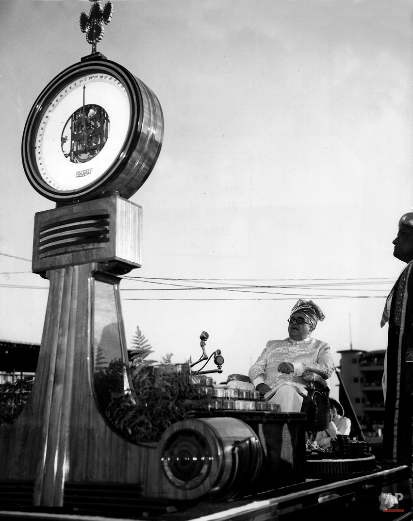 The Aga Khan III celebrates his 60th anniversary as head of the Ismaili Muslim sect by balancing himself against a matching weight of diamonds at Bradbourne Stadium, Bombay, India,  March 10, 1946.  He is shown as the containers of diamonds equal his weight and the scale nears zero.  The monetary equivalent of the diamonds was to be donated to charity.  (AP Photo/Max Desfor)