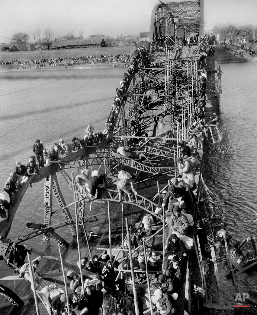 Residents from Pyongyang, North Korea, and refugees from other areas crawl perilously over shattered girders of the city's bridge on Dec. 4, 1950, as they flee south across the Taedong River to escape the advance of Chinese Communist troops. The Chinese entered the Korean War as allies of North Korea.  U.S. troops battled on the side of South Korea.   Begun in June 25, 1950, the war ended on July 27, 1953, with a military demarcation line set near the 38th parallel where it started. Korea remains divided.   (AP Photo/Max Desfor)