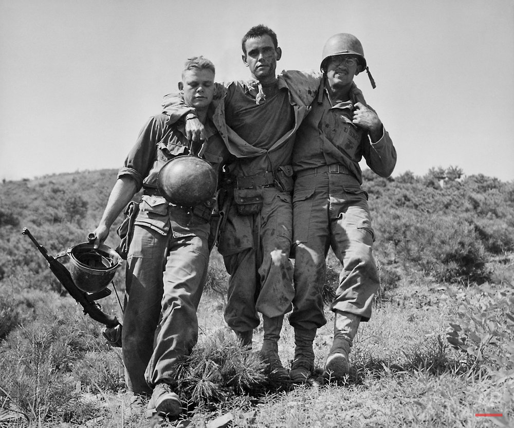 "In August 1950 photo, U.S. Marines help a wounded buddy on the Naktong River front in South Korea. The war that began in Korea 60 years ago, on June 25, 1950, a ghastly conflict that killed millions and left the peninsula in ruins, became ""The Forgotten War"" in many American minds. (AP Photo/Max Desfor)"