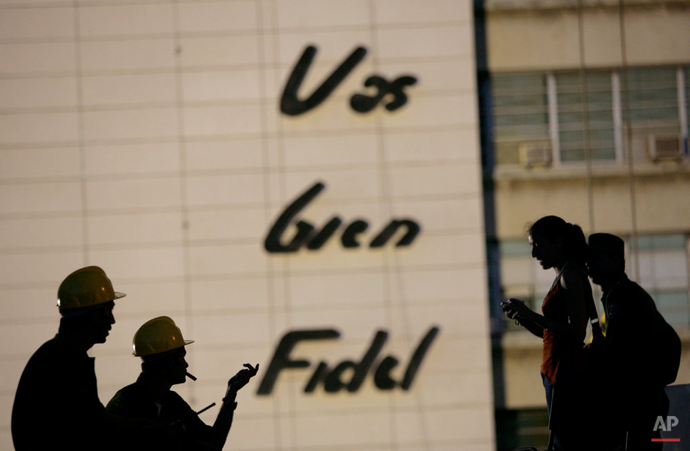 "Workers talk next to a wall where a sculpture in honor of the late revolutionary commander Camilo Cienfuegos will be installed at the Revolution square in Havana, Monday, Oct. 26, 2009. The sculpture, created by artist Enrique Avila, will be inaugurated on Wednesday to commemorate the 50th anniversary of Cienfuegos' death. The writing on the wall reads in Spanish ""You are going well Fidel"". (AP Photo/Franklin Reyes)"