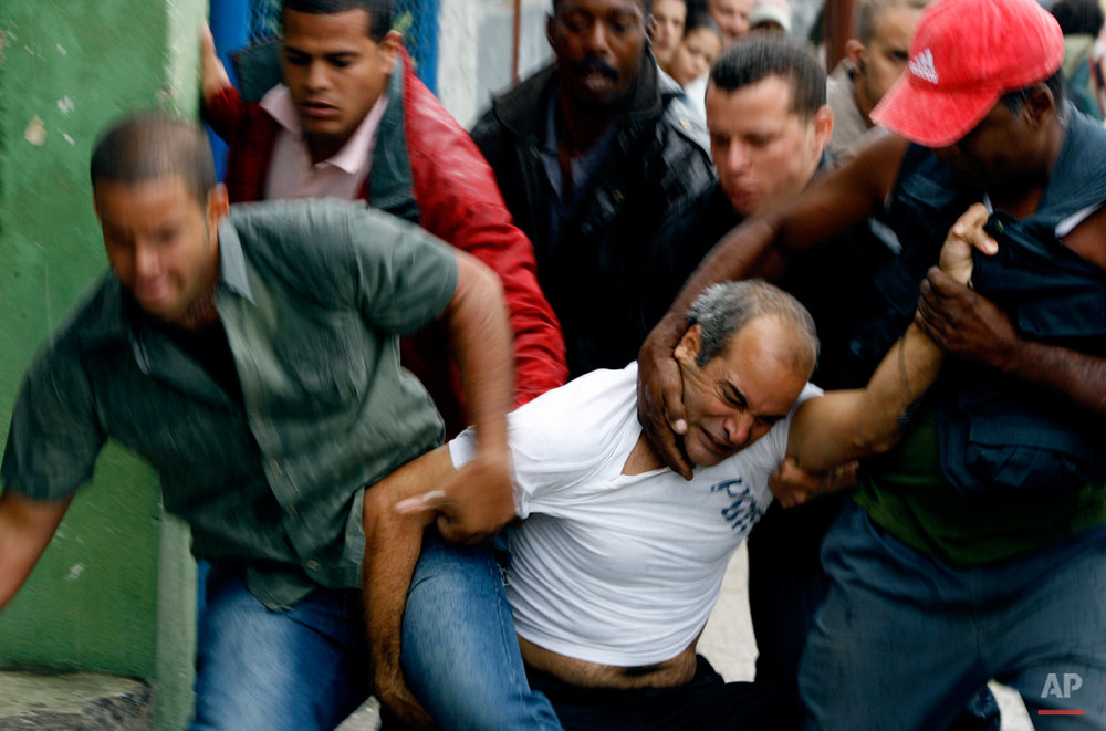 A demonstrator is taken away from the street by security agents during a protest in Havana, Wednesday, March 17, 2010. Cuban security agents prevented Ladies in White, a group of female dissidents, from marching on the outskirts of the capital to demand the release of their jailed husbands and sons, physically removing them when they lay down in the street in protest. (AP Photo/Franklin Reyes)