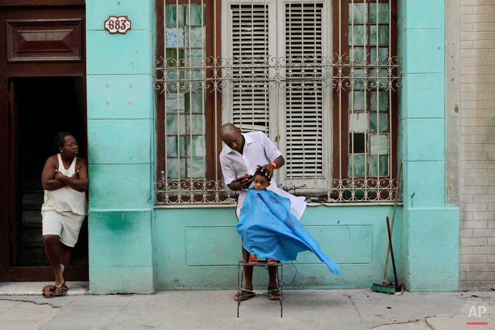 Barber Orlando Gonzalez cuts the hair of young client Maikol as Gonzalez' sister Cilia looks on along a sidewalk in Havana, Cuba, Wednesday Oct. 6, 2010. (AP Photo/Franklin Reyes)