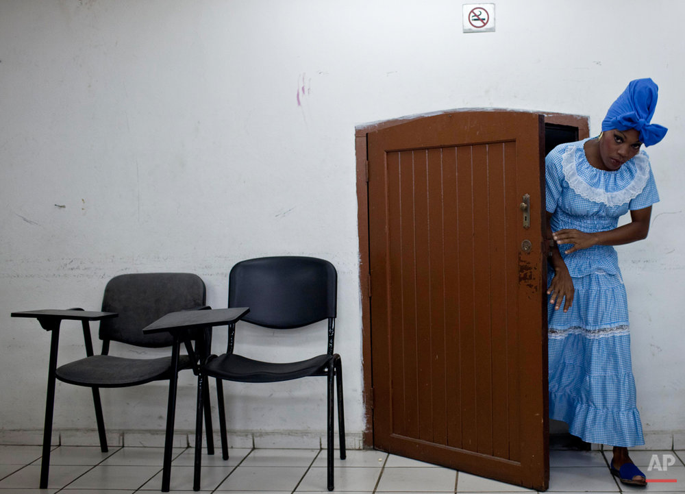 In this May 23, 2014 photo, Yusanelis Moras leaves of a room before a performance in Havana, Cuba. Obini Bata is the first orchestra of percussionists made up of women who dared to drum bata drums. Under Afro-Cuban beliefs, the two-sided bata (pronounced ba-TAHí) are sacred, used for connecting with Santeria spirits. Tradition dictates the drums be made only from the hides of male goats. Players must undergo a lengthy consecration ritual. And, above all, the sacred bata are only to be played by men. (AP Photo/Franklin Reyes)