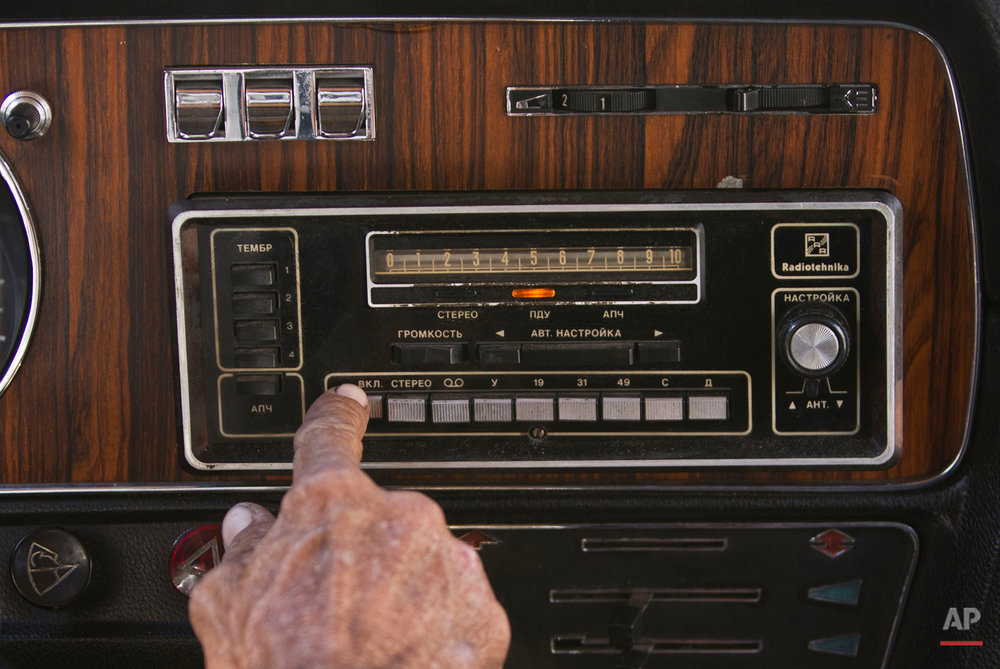"""In this June 18, 2014 photo, taxi driver Moises Suarez pushes a radio knob inside a Soviet-made limousine taxi cab in Havana, Cuba. In a former life it was one of the  """"comandante's"""" cars: A fleet of black, boxy, Soviet-made limousines that for years were at the disposal of the presidency in Fidel Castro's Cuba. Today the limos have been decommissioned and repurposed as Havana taxi cabs, at the service of tourists who want a little slice of history to go with their ride across town. (AP Photo/Franklin Reyes)"""