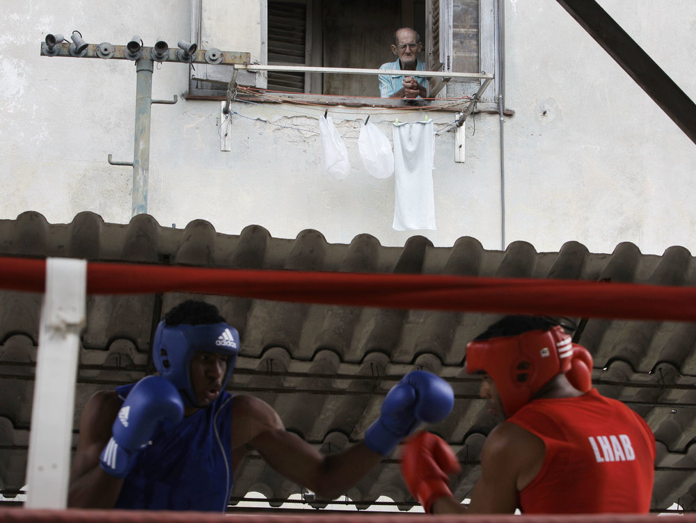 In this March 9, 2013 photo, a man peers from his home's window to watch boxer Frank Sanchez, left, fight with Julio Bernal during a boxing tournament at the Rafael Trejos boxing gym in Old Havana, Cuba. In 1961, two years after the Cuban Revolution, all professional sports were banned and the very concept has been anathema to the island government�s Marxist ideals ever since. Now the island is on the verge of partially reversing five decades of strictly amateur boxing. (AP Photo/Franklin Reyes)