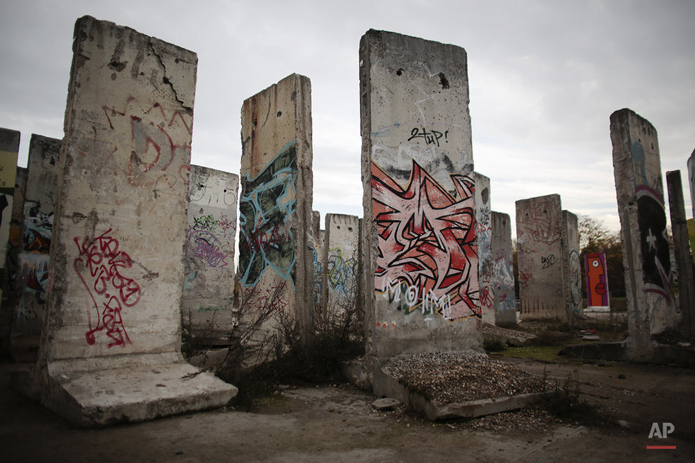 In this Nov. 3, 2014 photo original elements of the former Berlin wall are displayed for sale at the area of a construction material merchant at the village Teltow near Berlin. On Nov. 9, 2014, Germany celebrate the 25th anniversary of the fall of the wall on Nov. 9, 1989. After 25 years only a few remains of the wall remind of the about 160 kilometers (about 100 miles) long border which surrounded the west part of Berlin. (AP Photo/Markus Schreiber)