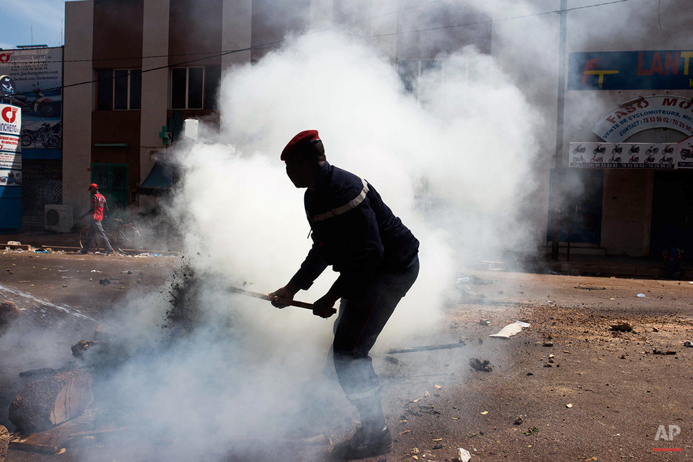 A Burkina Faso Policeman try's to extinguish a fire as he and others clash with protesters as that are protesting against their longtime president that seeks another term in Ouagadougou, Burkina Faso, Tuesday, Oct. 28, 2014, . Police used tear gas on Tuesday to disperse an opposition protest in Burkina Faso's capital, as tensions increase ahead of a vote this week on whether the country's longtime president can seek another term.  (AP Photo/Theo Renaut)