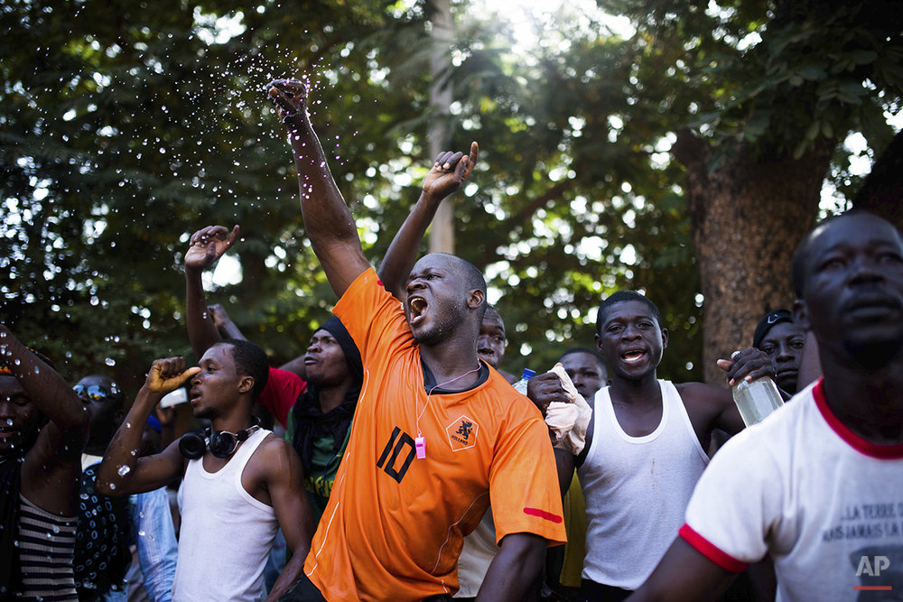 In this photo taken Thursday, Oct. 30, 2014, protesters shout out as they go on a rampage near the parliament building in Burkina Faso as people protest against their longtime President Blaise Compaore who seeks another term, in Ouagadougou, Burkina Faso. Protesters stormed the parliament Thursday, dragging furniture and computers onto the street and setting the main chamber ablaze, in the most significant challenge to the president's rule during his 27 years in power. (AP Photo/Theo Renaut)