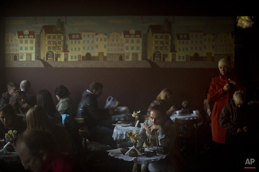 Patrons sit in a coffee shop in central Kiev, Ukraine, Saturday, Oct. 25, 2014. (AP Photo/Emilio Morenatti)