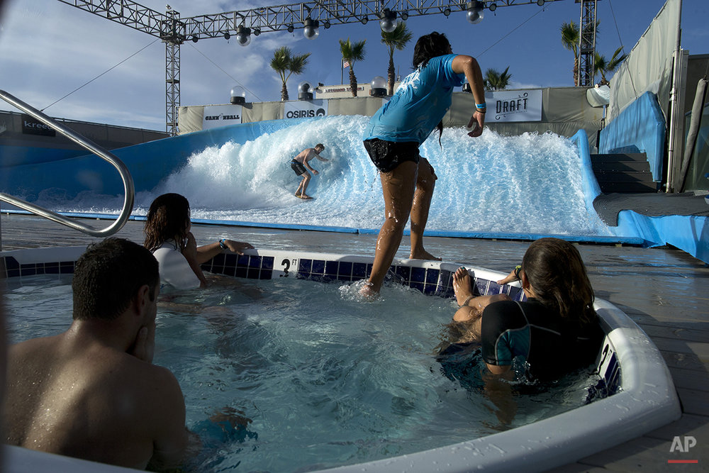 AP10ThingsToSee - A man rides a wave at the Wavehouse as others stay warm in a Hot tub, Tuesday, Oct. 21, 2014, in San Diego. The machine-generated wave provides surfers on finless boards a chance to hone their skills, just a few feet from a San Diego beach. (AP Photo/Gregory Bull)