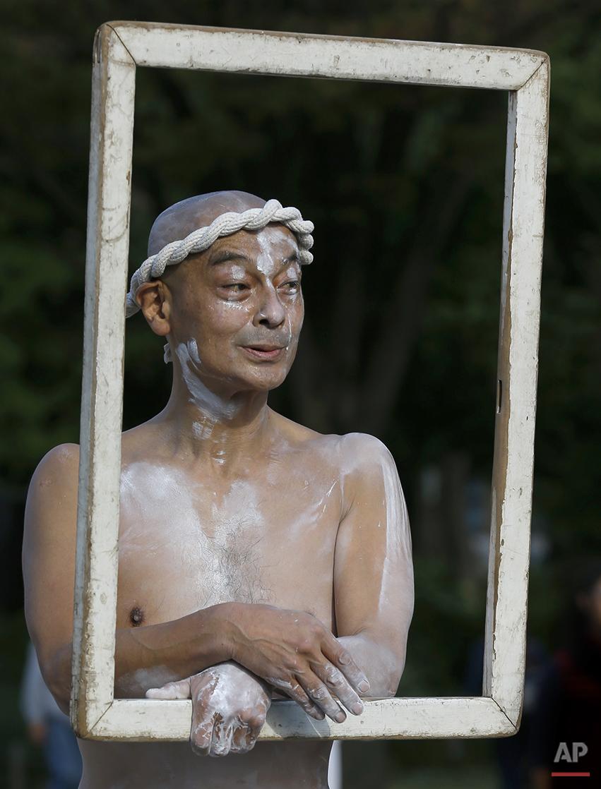 Street performer Taro Yukitake performs his Leonardo da Vinci's Mona Lisa at a park in Tokyo, Sunday, Oct. 26, 2014. (AP Photo/Shizuo Kambayashi)