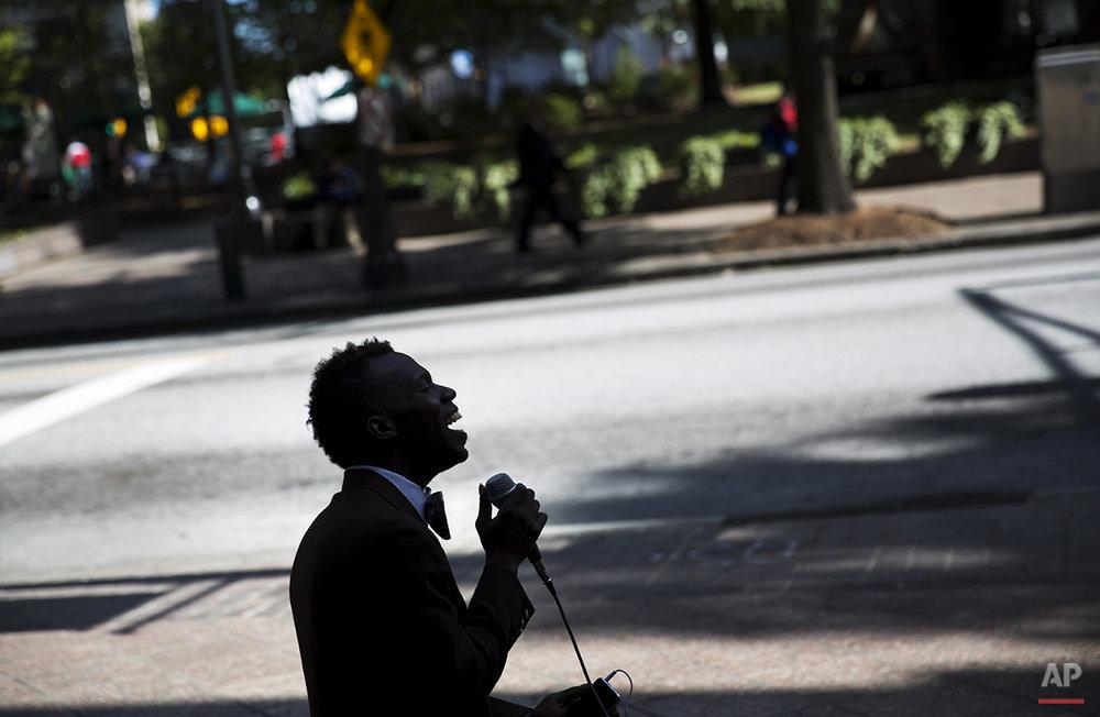 "Nathaniel Marcqiese Rainey, 28, sits along Peachtree Street while singing Ray Charles' ""Georgia on My Mind,"" Thursday, Oct. 23, 2014, in Atlanta. (AP Photo/David Goldman)"