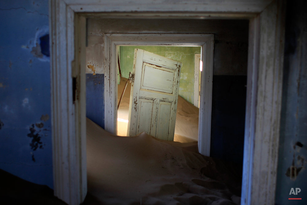 In this July 23, 2013 photo, sand fills an abandoned house in Kolmanskop, Namibia. Kolmanskop, was a diamond mining town south of Namibia, build in 1908 and deserted in 1956. SInce then, the desert slowly reclaims its territory, with sand invading the buildings where 350 German colonists and more than 800 local workers lived during its hay-days of the 1920s. (AP Photo/Jerome Delay)