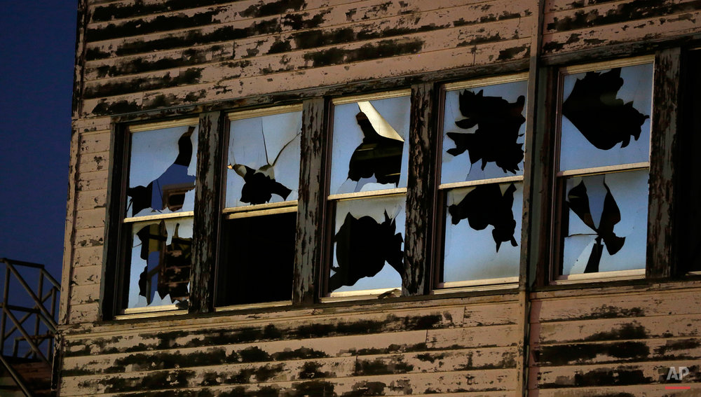 In this Oct. 2, 2014, dusk falls on the shattered windows of the reemployment center at the former Mare Island Naval Shipyard in Vallejo, Calif. The shipyard dates from the 1850s and was the first U.S. Navy base in the Pacific. At its peak in World War II some 50,000 worked on the island. Today about 4,000 either work, live or go to school there. A number of its buildings and facilities are still empty following the closing of the shipyard in 1996. The building is to be demolished soon. (AP Photo/Eric Risberg)