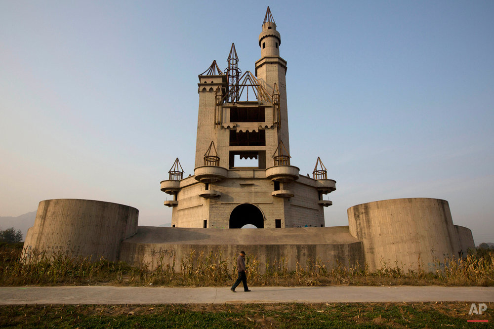 In this Oct. 18, 2014, photo, a man walks past the shell of a castle-like building that was once destined to be part of Asia's biggest amusement park in Beijing, China. Work halted on the project in 1998 due to financial problems and the site has been left as it is until 2013 when developers demolished other parts of the massive park for redevelopment. The castle-like building however remains untouched and a reminder of better times in that part of Beijing's periphery. (AP Photo/Ng Han Guan)