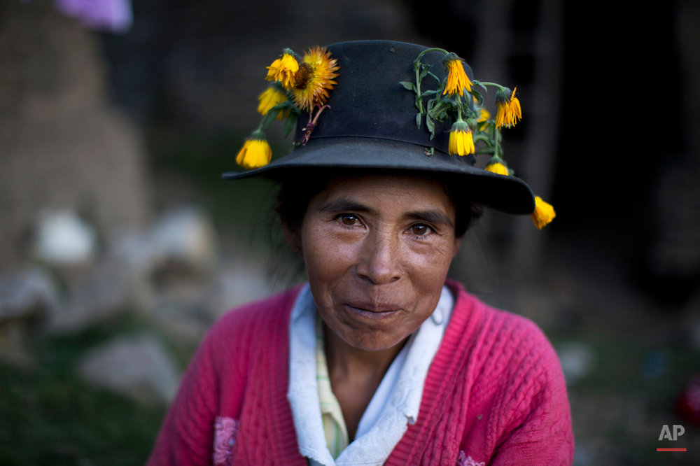 In this Oct. 29, 2014 photo, Gregoria Huaman poses for a portrait in her flower covered hat, common among women in the area, after burying her brother in law, Felix Huama, in Huallhua in Peru's Ayahuanco region. Felix Huaman and his brother-in-law Narcizo Cusiche were killed on June 14, 1990 while defending the town as members of the citizen self-defense force, so that villagers could escape from Shining Path militants, but their remains were only recently exhumed. Hundreds of such cases, most until now barely registered, are coming to light as forensic anthropologists methodically unearth victims of Peruís 1980-2000 dirty war absent government fanfare. (AP Photo/Rodrigo Abd)