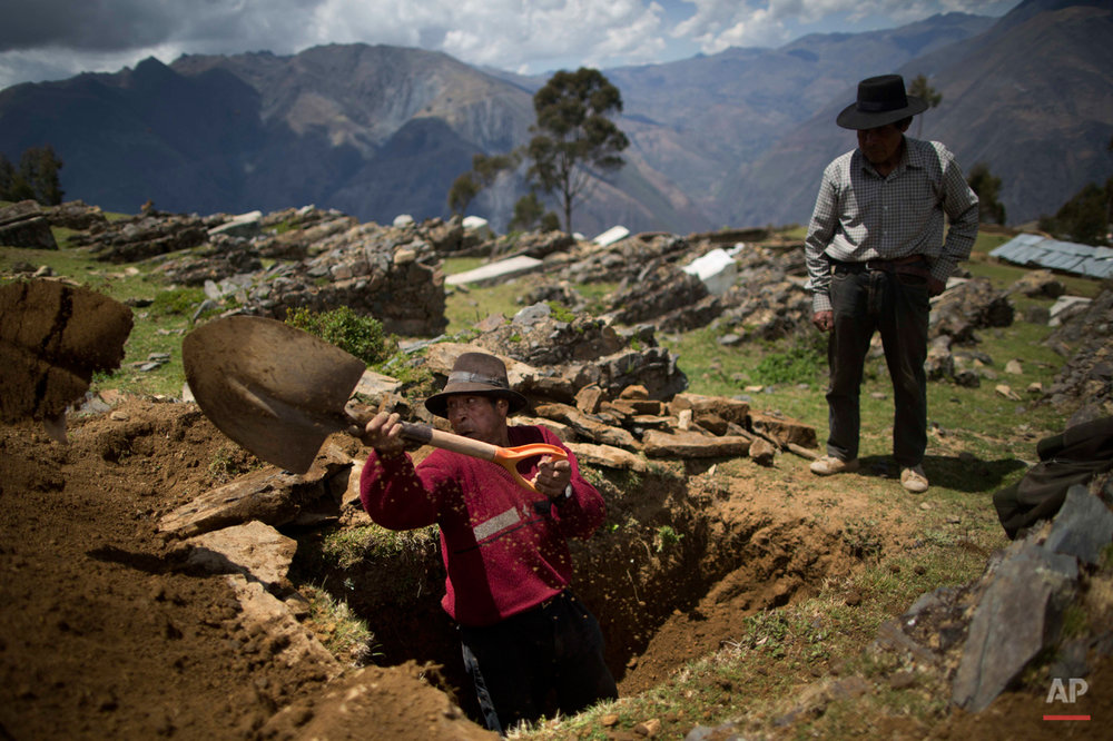 In this Oct. 29, 2014 photo, Dionisio Mulla digs a grave for his brother-in-law Felix Huaman in Huallhua in Peru's Ayahuanco region. Felix was killed 24 years ago while defending their town with two other men, so villagers could escape from Shining Path militants. However their remains were exhumed only last year and recently handed over to relatives. (AP Photo/Rodrigo Abd)