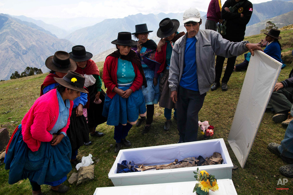 In this Oct. 29, 2014 photo, relatives and friends pay their final respects to three villagers who died defending their town in Huallhua in Peru's Ayahuanco region. Nestor Curo, Felix Huaman and Narcizo Cusiche were killed 24 years ago while defending their town so villagers could escape from Shining Path militants. However their remains were exhumed only last year and recently handed over to relatives. Huaman was age 50, the other two men were in their 20s. (AP Photo/Rodrigo Abd)