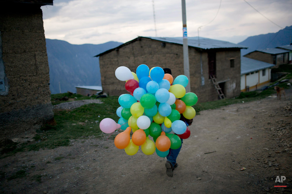 In this Oct. 28, 2014 photo, a government social worker carries balloons after a training course for young leaders in Ayahuanco, Peru. Though the Shining Path was defeated two decades ago, cocaine-funded rebel remnants continue to hound Peruís security forces in the remote region. (AP Photo/Rodrigo Abd)