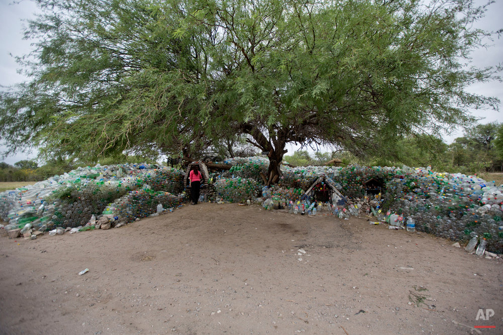 "In this Nov. 1, 2014 photo, a woman visits a roadside sanctuary for ""La Difunta Correa"" full of water bottles in Cordoba, Argentina. Legend has it that Deolinda Correa died in the 1840's while fruitlessly searching in the desert for her husband who was drafted to fight in the civil war. Correa, carrying her baby with her, died of thirst and exhaustion. The people who found her body discovered her son was still alive, nursing on her breast to survive. Today people erect sanctuaries along the nation's roads, leaving bottles of water to quench her eternal thirst . (AP Photo/Natacha Pisarenko)"