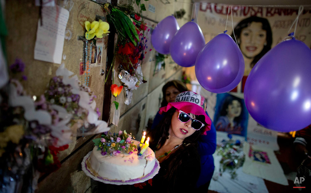 In this Saturday, Oct. 11, 2014 photo, Flavia Piana holds a cake she made as she sings happy birthday to the late Argentine singer Gilda where the singer is buried at the Chacarita cemetery on what would have been Gilda's birthday in Buenos Aires, Argentina. Cumbia singer Miriam Alejandra Bianchi was born in 1961, and her stage name Gilda was in tribute to Rita Hayworth. She became one of Argentinaís most popular folk saints after she was killed in a bus accident when she was just 35. People gather at her tomb to honor her and thank for her miracles. (AP Photo/Natacha Pisarenko)