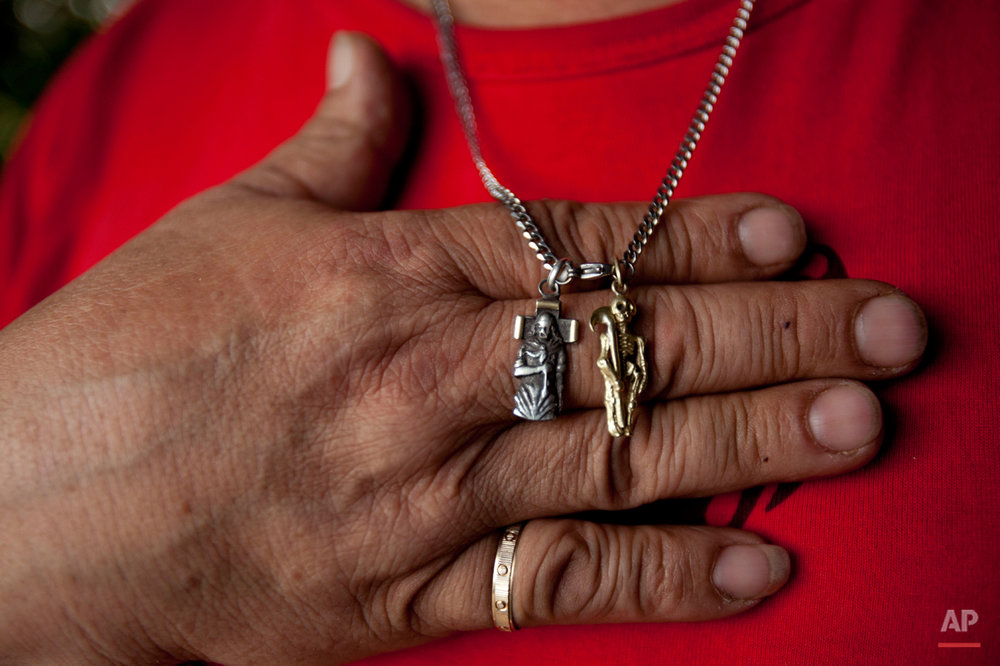 In this Oct. 8, 2014 photo, Carlos Marquez shows his pendants of San La Muerte, right, and Gauchito Gil at his home in the Carcova slum on the outskirts of Buenos Aires,  Argentina. Marquez said he grew up following Gauchito Gil, who he considers the folk saint of the poor and needy, referring to both material and spiritual poverty. His devotion to San La Muerte began in prison, where he served 15 years for armed robbery. (AP Photo/Natacha Pisarenko)