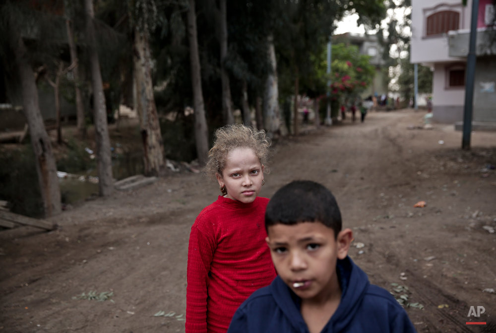 In this Wednesday, Nov. 5, 2014 photo, Egyptian school children walk on a street, near the home of 13-year-old Sohair el-Batea who died undergoing the procedure of female genital mutilation performed by Dr. Raslan Fadl, in Dierb Biqtaris village, on the outskirts of the town of Aga in Dakahliya,120 kilometers (75 miles) northeast of Cairo, Egypt. Fadlís continued work demonstrates the challenges to curbing FGM in Egypt, which has one of the highest rates of the practice in the world, at more than 90 percent. The operation involves removing the clitoris and all or part of the labia minora, according to UNICEF. (AP Photo/Nariman El-Mofty)