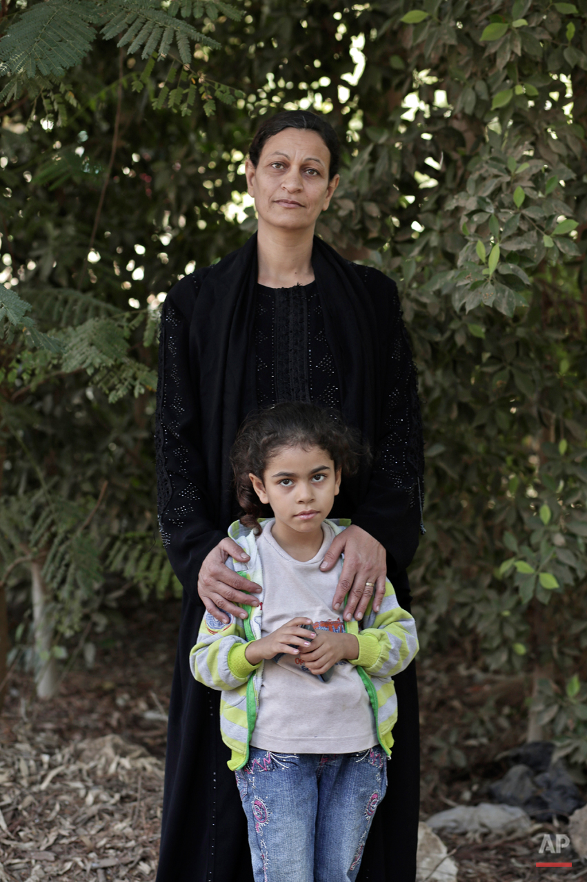 In this Saturday, Nov. 15, 2014 photo, Hamdeya Nazmy, 43, who was forcefully subjected to female genital mutilation as a 9-year-old child poses for a photograph with her 5-year-old daughter Demyana, in Sidfa, 340 kilometers (210 miles) south of Cairo, Egypt. Nazmy has seven daughters and only one was   submitted to female genital cutting. Genital mutilation involves removing all or part of the clitoris and labia minora. It is practiced in 29 countries, most of them in East and West Africa, but also in Egypt and parts of Iraq and Yemen. (AP Photo/Nariman El-Mofty)