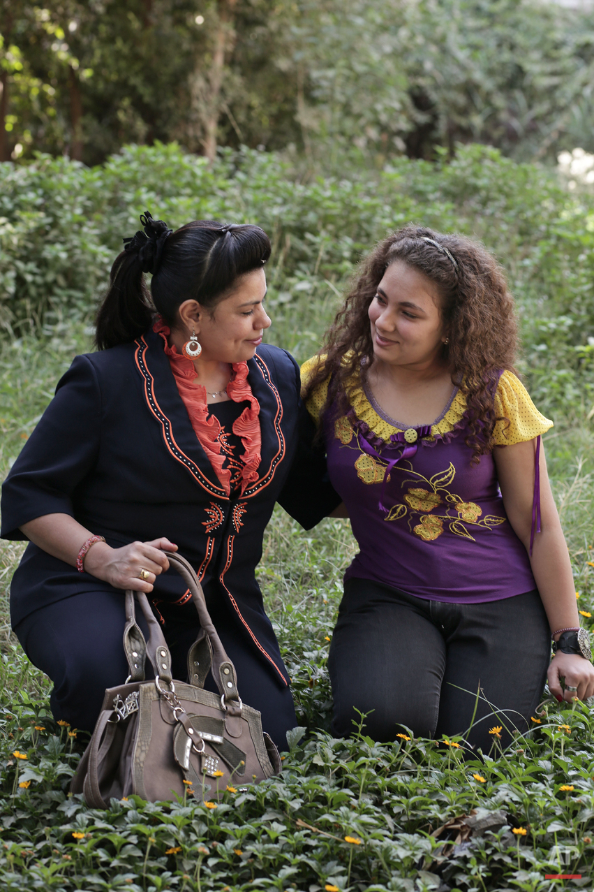 "In this Saturday, Nov. 15, 2014 photo, Egyptian Coptic Christian Manal Nasef Fahmy, 35, poses for a photograph with her 17-year-old daughter Marina, who were both subjected to female genital mutilation in Sidfa, 340 kilometers (210 miles) south of Cairo, Egypt. ""The midwife came to our home. My father took me far away so I don't hear my older sister screaming as she underwent the operation. I was next after my sister and I will never forget it,"" she said. Manal had a doctor circumcise her daughter Marina without anesthesia. ""I decided to have her circumcised before being educated about it. I will always regret it,"" Manal said. (AP Photo/Nariman El-Mofty)"