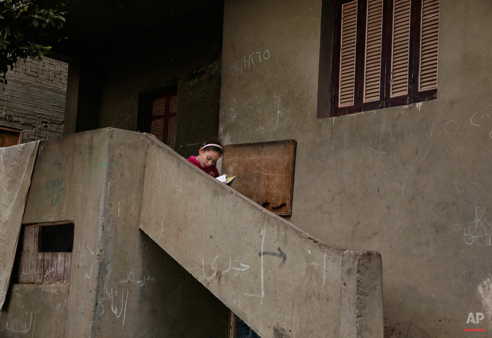 In this Wednesday, Nov. 5, 2014 photo, an Egyptian girl reads a book on a stairway, near the home of 13-year-old Sohair el-Batea who died undergoing the procedure of female genital mutilation performed by Dr. Raslan Fadl, in Dierb Biqtaris village, on the outskirts of Aga town in Dakahliya,120 kilometers (75 miles) northeast of Cairo, Egypt. Fadlís continues to work demonstrating the challenges to curbing FGM in Egypt, which has one of the highest rates of the practice in the world, at more than 90 percent. (AP Photo/Nariman El-Mofty)