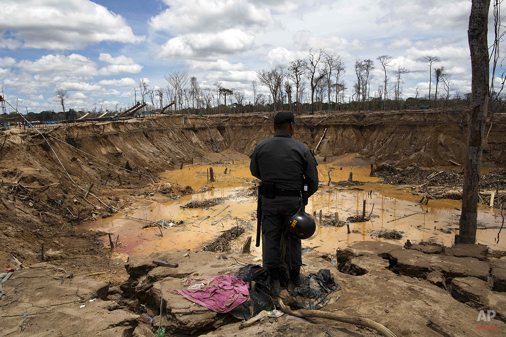 In this Nov. 11, 2014 photo, a policeman stands before an abandoned crater created by gold mining, after police shutdown activity during an operation to eradicate illegal gold mining camps in the area known as La Pampa, in Peru's Madre de Dios region. Less than a month before Peru plays host to global climate talks, the government sent a battalion of police into the southeastern jungles to dismantle illegal gold-mining mining camps. In addition to contributing to deforestation, the illegal alluvial gold mining contaminates the jungle with tons of mercury. (AP Photo/Rodrigo Abd)