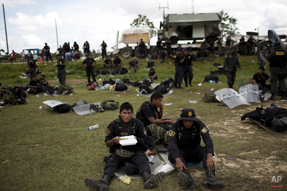 In this Nov. 12, 2014 photo, policemen eat lunch at a makeshift base, after taking part in an operation to eradicate illegal gold mining camps in the area known as La Pampa, in Peru's Madre de Dios region. Less than a month before Peru plays host to global climate talks, the government sent a battalion of police into southeastern jungles to dismantle illegal gold-mining mining camps. In addition to contributing to deforestation, the illegal alluvial gold mining contaminates the jungle with tons of mercury. (AP Photo/Rodrigo Abd)