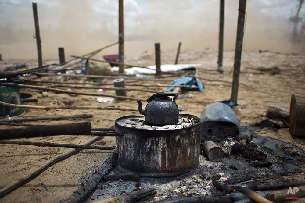 In this Nov. 12, 2014 photo, a charred kettle sits on top of a scorched makeshift stove in an illegal gold mining camp, set ablaze by police as part of an operation to eradicate the illegal mining camps in the area known as La Pampa, in Peru's Madre de Dios region. Less than a month before Peru plays host to global climate talks, the government sent a battalion police into southeastern jungles to dismantle illegal gold-mining mining camps. Police destroyed motors and dynamited a dozen motorcycles as they tore down dwellings that included at least one mud-flanked bordello. (AP Photo/Rodrigo Abd)
