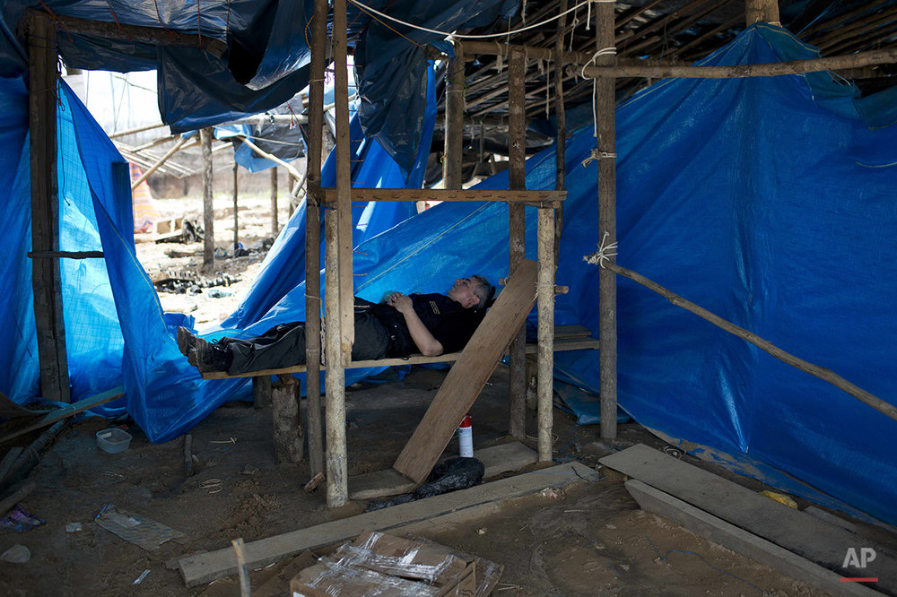In this Nov. 11, 2014 photo, a policeman takes a nap on a wooden slat, in an illegal gold mining camp after it was occupied in a police operation to eradicate illegal gold mining camps in the area known as La Pampa, in Peru's Madre de Dios region. Less than a month before Peru plays host to global climate talks, the government sent a battalion of police into southeastern jungles to dismantle illegal gold-mining mining camps. (AP Photo/Rodrigo Abd)