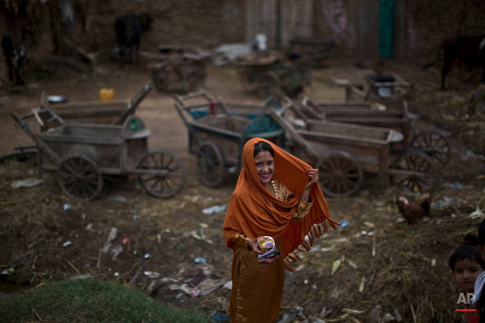 An Afghan refugee, wearing new clothes, smiles to her friends while she and others celebrate the Muslim holiday of Eid al-Adha, or Feast of Sacrifice, on the outskirts of Islamabad, Pakistan, Monday, Oct. 6, 2014. Muslims around the world celebrate Eid to commemorate what Muslims believe was Prophet Abraham's willingness to sacrifice his son Ismail. Because the holiday follows the Muslim lunar calendar that depends on sightings of the moon, the holiday starts on Monday in Pakistan. (AP Photo/Muhammed Muheisen)
