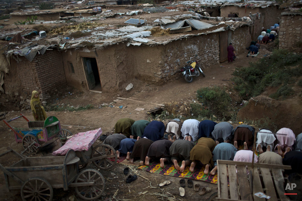 Afghan refugees and internally displaced Pakistanis from tribal areas, offer Eid al-Adha prayers, on the outskirts of Islamabad, Pakistan, Monday, Oct. 6, 2014. Muslims around the world celebrate the Muslim holiday of Eid al-Adha, or Feast of Sacrifice, to commemorate what Muslims believe was Prophet Abraham's willingness to sacrifice his son Ismail. Because the holiday follows the Muslim lunar calendar that depends on sightings of the moon, the holiday starts on Monday in Pakistan. (AP Photo/Muhammed Muheisen)