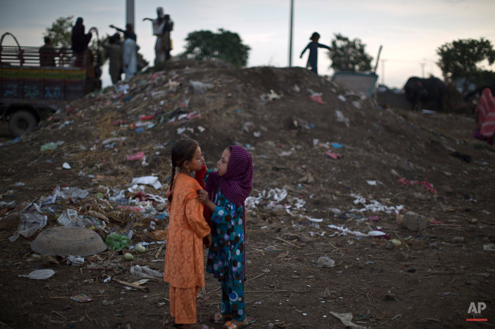 An Afghan refugee applies makeup to her friend as they celebrate the Muslim holiday of Eid al-Adha, or Feast of Sacrifice, on the outskirts of Islamabad, Pakistan, Monday, Oct. 6, 2014. Muslims around the world celebrate Eid al-Adha, or the Feast of the Sacrifice, to commemorates what Muslims believe was Prophet Abraham's willingness to sacrifice his son Ismail. Because Eid follows the Muslim lunar calendar that depends on sightings of the moon the holiday starts on Monday in Pakistan. (AP Photo/Muhammed Muheisen)