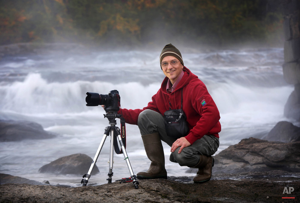 A.P. staff photographer Robert F. Bukaty poses while shooting a feature photo at the Royal River in Yarmouth, Maine, Monday, Oct. 6, 2014.  (AP Photo/Robert F. Bukaty)