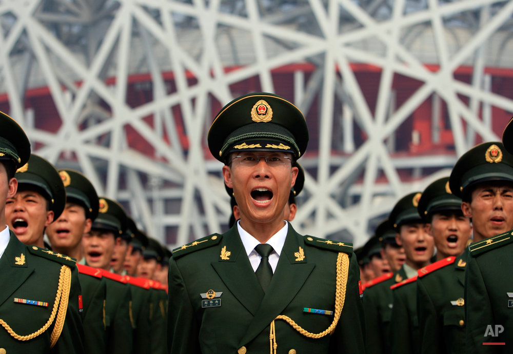 Chinese paramilitary police officers take an oath to ensure safety during the 2008 Beijing Olympics, in a drill outside the Bird's Nest National Stadium, Wednesday, July 23, 2008, in Beijing.  (AP Photo/Robert F. Bukaty)