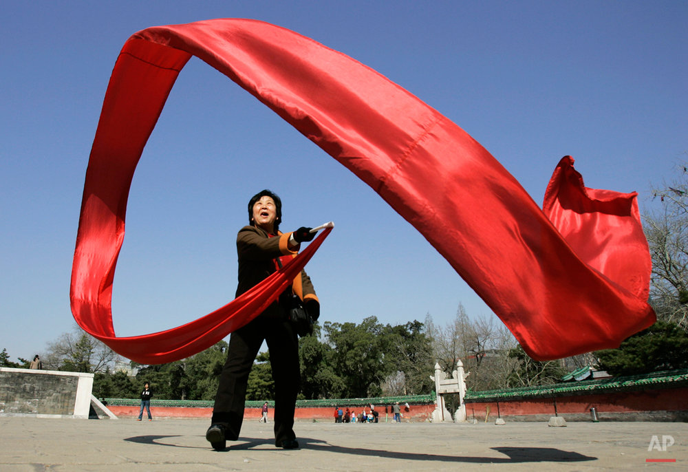 A woman waves a large red ribbon in a sweeping figure-eights as part of her morning exercise at Ritan Park, Friday, April 4, 2008, In Beijing. (AP Photo/Robert F. Bukaty)