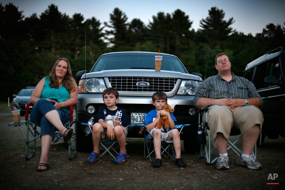 In this photo made Thursday, June 26, 2014, Jen and Philip Mason, along with their sons Skyelar, left, and Trysten, watch the previews at the Saco Drive-In in Saco, Maine. Many in the movie industry feared the need to convert to digital could be the death knell for drive-ins, but drive-in operators are finding creative ways to afford the switch.  Drive-in movie theater operators say more than 200 of the remaining 348 drive-ins in the country have made the expensive conversion from film to digital, which typically costs more than $70,000.  (AP Photo/Robert F. Bukaty)