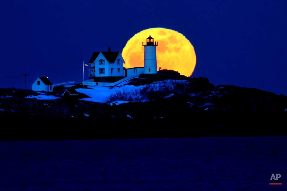 The full moon rises behind Cape Neddick Light, also known as Nubble Light, Feb. 9, 2009, in York, Maine. The February full moon is known as the snow moon. (AP Photo/Robert F. Bukaty)