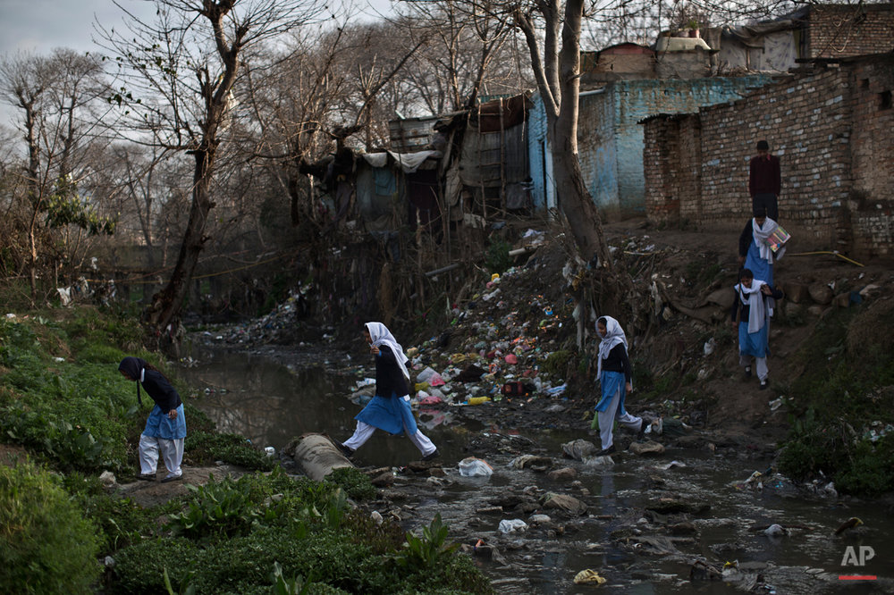 In this Tuesday, March 4, 2014, photo, Pakistani schoolgirls cross a stream of sewage and rubbish that separates their neighborhood from the main road, heading to their school in Islamabad, Pakistan. Malala Yousafzai's struggle for girls to be educated in a deeply conservative society led to her shooting by the Taliban two years ago, while her relentless campaign for women's was rewarded Friday, Oct. 10, 2014, by the recognition of her work as she was jointly awarded the Nobel Peace Prize. (AP Photo/Muhammed Muheisen)
