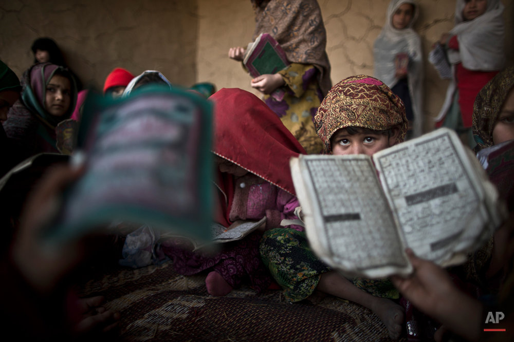 In this Tuesday, Jan. 28, 2014, photo, Pakistani children, whose families were displaced from Pakistan's tribal areas due to fighting between the Taliban and the army, hold booklets of Urdu alphabets and verses of the Quran, and repeat after their teacher during their daily Madrassa, or Islamic school, at a mosque on the outskirts of Islamabad, Pakistan. Malala Yousafzai's struggle for girls to be educated in a deeply conservative society led to her shooting by the Taliban two years ago, while her relentless campaign for women's was rewarded Friday, Oct. 10, 2014, by the recognition of her work as she was jointly awarded the Nobel Peace Prize. (AP Photo/Muhammed Muheisen)